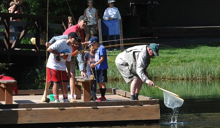 In this photo taken on June 16, 2015, a small crowd of onlookers gathers as Dave Dunahay scoops up a feisty rainbow for a young angler during Next Cast Flyfishers camp at Shevlin Park, in Bend, Ore. (Ryan Brennecke /The Bulletin via AP)