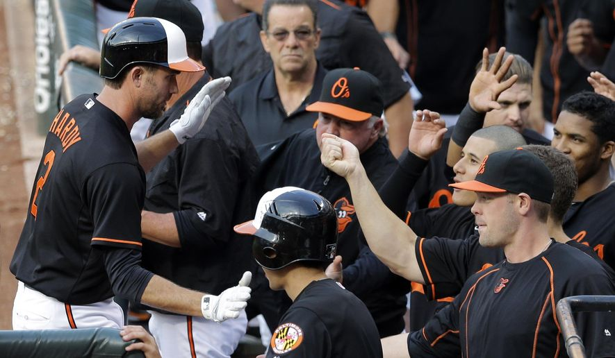 Baltimore Orioles' J.J. Hardy, left, high-fives teammates in the dugout after hitting a solo home run in the second inning of a baseball game against the Cleveland Indians, Friday, June 26, 2015, in Baltimore. (AP Photo/Patrick Semansky)