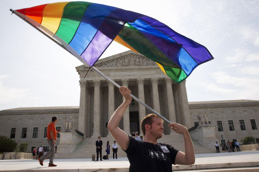 John Becker, 30, of Silver Spring, Md., waves a rainbow flag in support of gay marriage outside of the Supreme Court in Washington, Thursday June 25, 2015. The same-sex marriage ruling is among the remaining to be released before the term ends at the end of June. (AP Photo/Jacquelyn Martin)