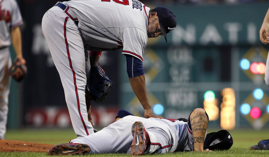 Atlanta Braves starting pitcher Williams Perez is checked by teammate Juan Uribe (2) as he lies on the ground after taking a line drive off his left leg during the fifth inning of a baseball game against the Pittsburgh Pirates in Pittsburgh, Friday, June 26, 2015. Perez faced two more batters and left the game. (AP Photo/Gene J. Puskar)