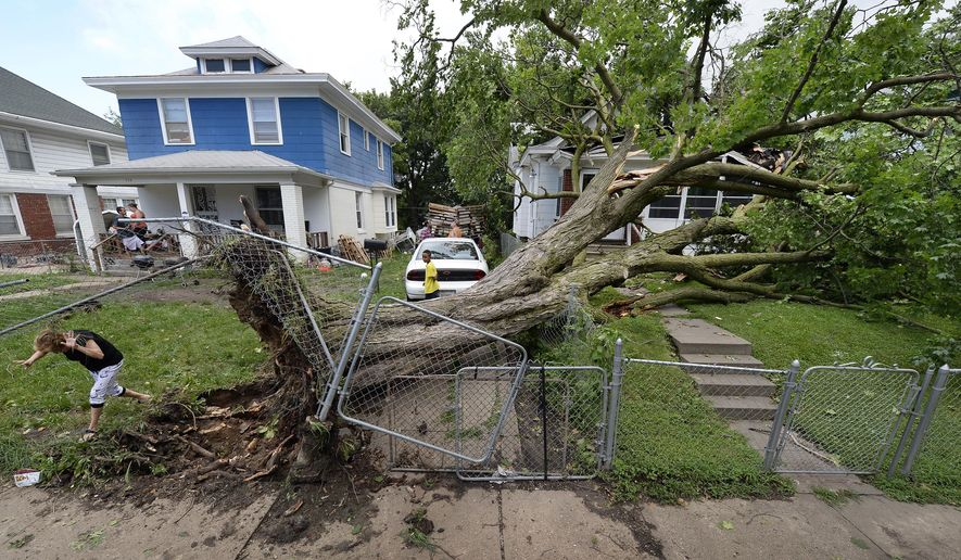 A uprooted tree from the yard of Jonathan Rogers, home at left, lies on Connie Dotson's lawn following overnight storms on Friday, June 26, 2015, in Kansas City, Mo. No one was injured. Storms with wind gusts up to 80 mph and torrential rains swept across Missouri overnight into Friday morning, leaving more than 150,000 homes and businesses without power and forcing dozens of water rescues. (Keith Myers/The Kansas City Star via AP)