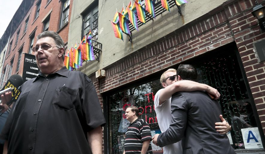 "Stonewall Inn's bartender who goes by the single name of Tree, far left, is interviewed while a couple, right, requesting anonymity,  kiss outside the iconic Greenwich Village bar, Friday, June 26, 2015, in New York.  ""I was here dancing with my friends the day of the rebellion when the cops raided the place,"" said Tree about 1969 event credited for igniting the gay rights movement. The Supreme Court declared Friday that same-sex couples have a right to marry anywhere in the U.S.  (AP Photo/Bebeto Matthews)"