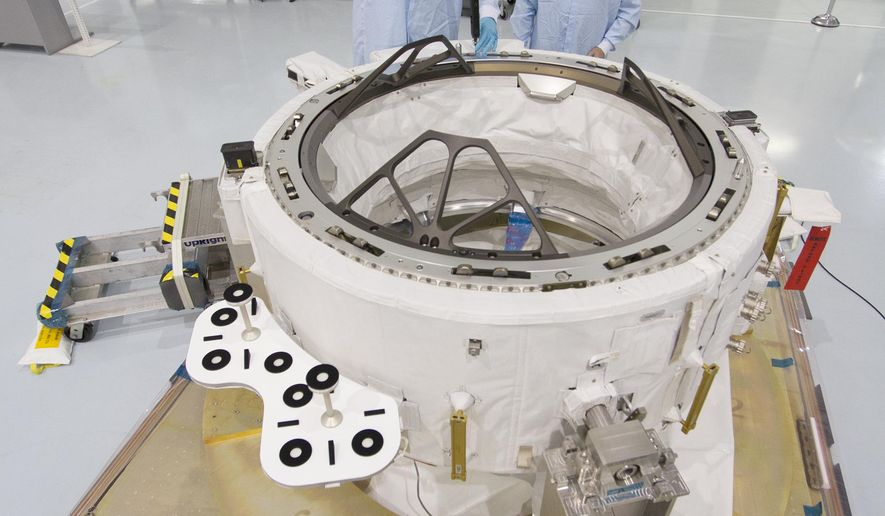 In this March 24, 2015 photo made available by NASA, engineers in the Space Station Processing Facility at the Kennedy Space Center in Cape Canaveral, Fla. check measurements on the International Docking Adapter. On Sunday, June 28, 2015, SpaceX is scheduled to launch a much-needed load of supplies and this new docking port to the International Space Station, on the heels of a failed supply run by Russia. (Cory Huston/NASA via AP)