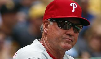 FILE - In this June 14, 2015, file photo, Philadelphia Phillies manager Ryne Sandberg stands in the dugout during a baseball game against the Pittsburgh Pirates in Pittsburgh. Sandberg resigned as manager of the baseball club on Friday, June 26, 2015. (AP Photo/Gene J. Puskar, File)