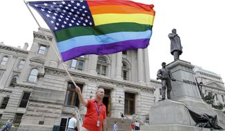 Scott Spychala waves a rainbow flag outside the Indiana Statehouse in Indianapolis, Friday, June 26, 2015 after the U.S. Supreme Court declared that same-sex couples have a right to marry anywhere in the US. (AP Photo/Michael Conroy)