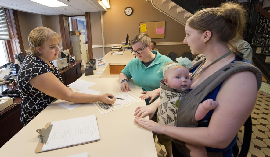 Deputy clerk Bettina Boughter, left, issues a marriage license to Amanda Ward, center, and Amanda Green, right (holding baby McKenna Ward) at the Pulaski County Court House Friday, June 26, 2015 in Little Rock, Ark. following a ruling by the US Supreme Court that struck down bans on same sex marriage nation wide. (AP Photo/Brian Chilson)