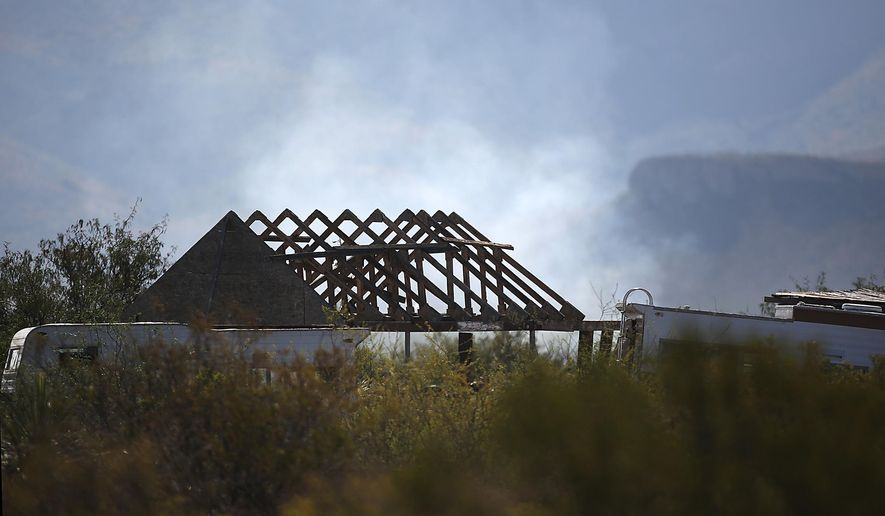 Smoke from an F-16 Fighting Falcon that crashed Wednesday night during a training with the 162nd Wing Arizona Air National Guard, is visible just beyond the construction of a home north of Douglas, Ariz., Thursday, June 25, 2015. The pilot's identity and condition is unknown at this time. (Mamta Popat/Arizona Daily Star via AP) ALL LOCAL TELEVISION OUT; PAC-12 OUT; MANDATORY CREDIT; GREEN VALLEY NEWS