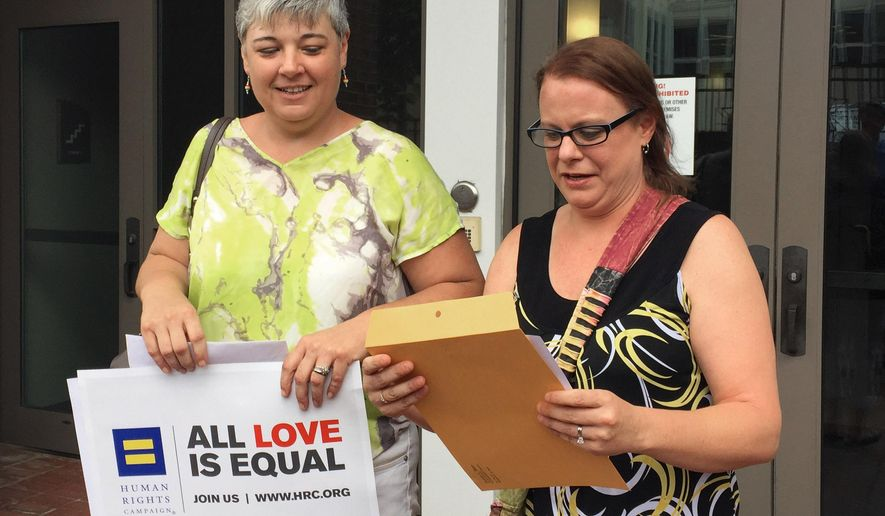 Newlyweds Jessica Dent, left, and Carolee Taylor leave a court building in Montgomery, Ala., with their wedding license on Friday, June 26, 2015. The two women were among the first same-sex couples to wed in Alabama after the U.S. Supreme Court ruled gay people can marry anywhere. (AP Photo/Kim Chandler)