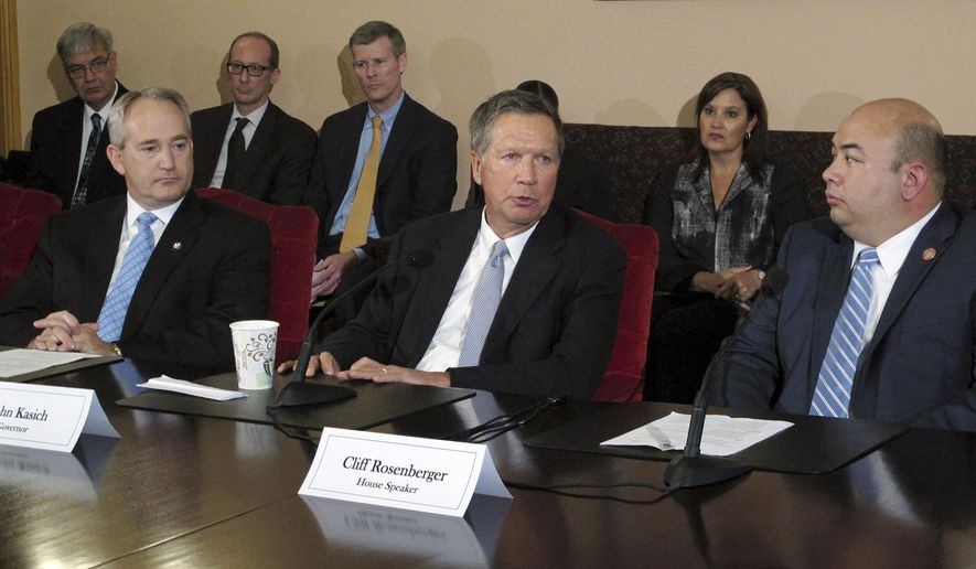 Ohio Gov. John Kasich, center, joins Senate President Keith Faber, left, and House Speaker Cliff Rosenberger, right, to discuss the state budget with reporters as other officials watch on Friday, June 26, 2015, at the Statehouse in Columbus, Ohio. (AP Photo/Kantele Franko)