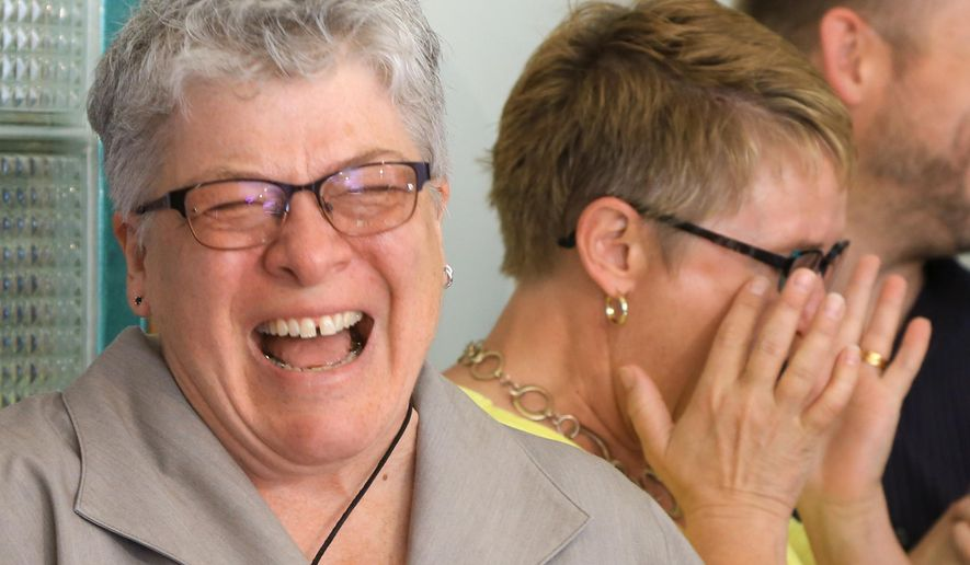 Marj Plumb, left, laughs with her wife Tracy Weitz, Friday, June 26, 2015, following a news conference to mark the U.S. Supreme Court's decision that sex couples have a right to marry anywhere in the United States. Plumb and Weitz are already married but until today their marriage was not recognized in Nebraska.  The court's 5-4 ruling means the remaining 14 states, in the South and Midwest, will have to stop enforcing their bans on same-sex marriage.(AP Photo/Nati Harnik)