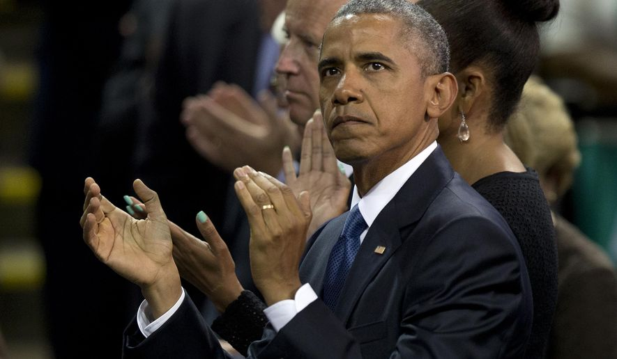 President Barack Obama stands in the audience with first lady Michelle Obama and Vice President Joe Biden, during services honoring the life of Reverend Clementa Pinckney, Friday, June 26, 2015, in Charleston, S.C., at the College of Charleston TD Arena. Pinckney was one of the nine people killed in the shooting at Emanuel AME Church last week in Charleston. (AP Photo/Carolyn Kaster)
