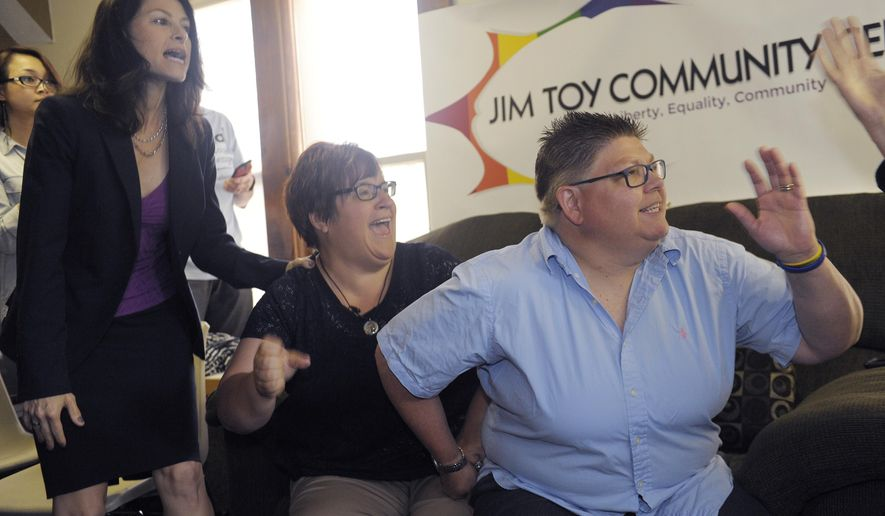 Jayne Rowse, right, and her partner April DeBoer and their attorney Dana Nessel celebrate the  U.S. Supreme Court decision on gay marriage on Friday, June 26, 2015 in Ann Arbor, Mich.  The court's 5-4 ruling means the remaining 14 states, in the South and Midwest, will have to stop enforcing their bans on same-sex marriage.  Michigan was one of the 14 states affected by the ruling. (Clarence Tabb Jr./Detroit News via AP)  DETROIT FREE PRESS OUT; HUFFINGTON POST OUT