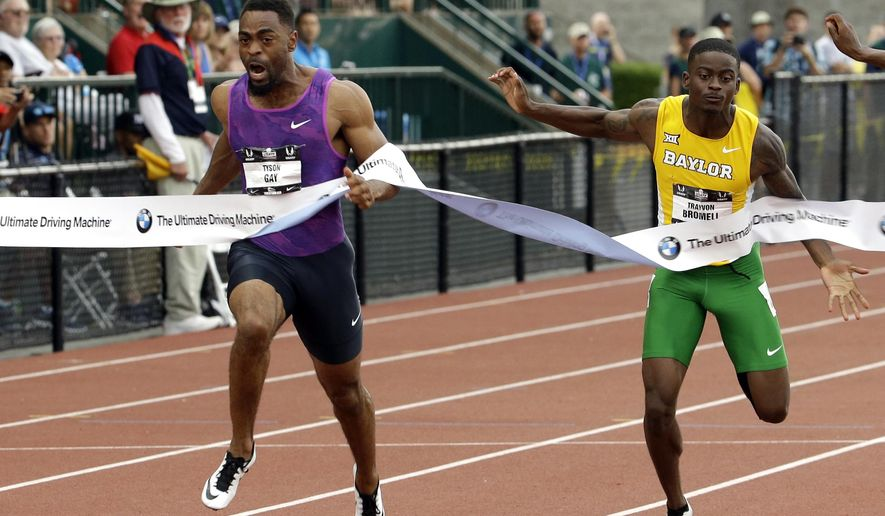 Tyson Gay, left, hits the tape ahead of Trayvon Bromell to win the 100-meter final at the U.S. Track and Field Championships in Eugene, Ore., Friday, June 26, 2015. (AP Photo/Don Ryan)