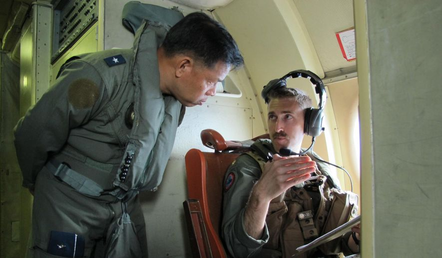 In this photo taken Thursday, June 25, 2015, Western Command deputy commander Brigadier General Guillermo Molina Jr. talks to U.S. Navy officer Patrick Ronan on board a P3 Orion plane during  the joint US-Philippines naval exercise dubbed CARAT (Cooperation Afloat Readiness and Training) 2015 over the Sulu Sea off Palawan Province in western Philippines. The weeklong combat exercises have helped the U.S. and Philippine navies prepare to jointly deal with natural disasters and a range of security challenges. (AP Photo/Jim Gomez) ** FILE **