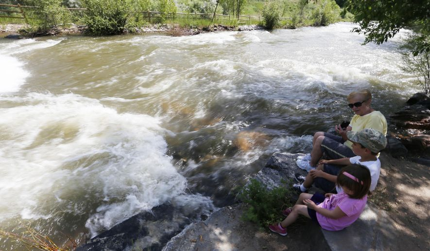 In this photograph taken Tuesday, June 23, 2015, Carol Johnston, back, sits with her grandchildren, Olivia, front, and Anthony Villano as water rushes by in Clear Creek in Golden, Colo. Authorities in two suburban Denver counties have banned access to the waterways following at least six rafting and tubing deaths so far this year. (AP Photo/David Zalubowski)
