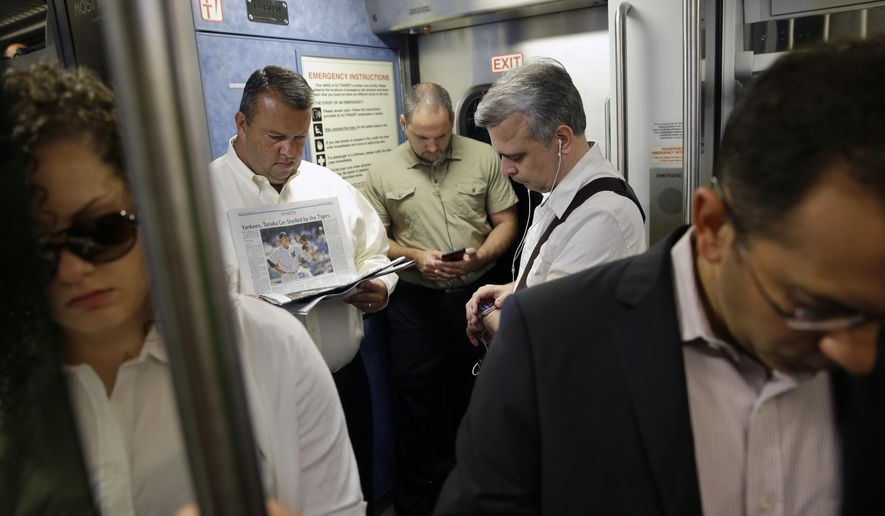Commuters read and check their phones as they stand on a New Jersey Transit passenger train to New York from Trenton, N.J., Monday, June 22, 2015. (AP Photo/Mel Evans) **FILE**