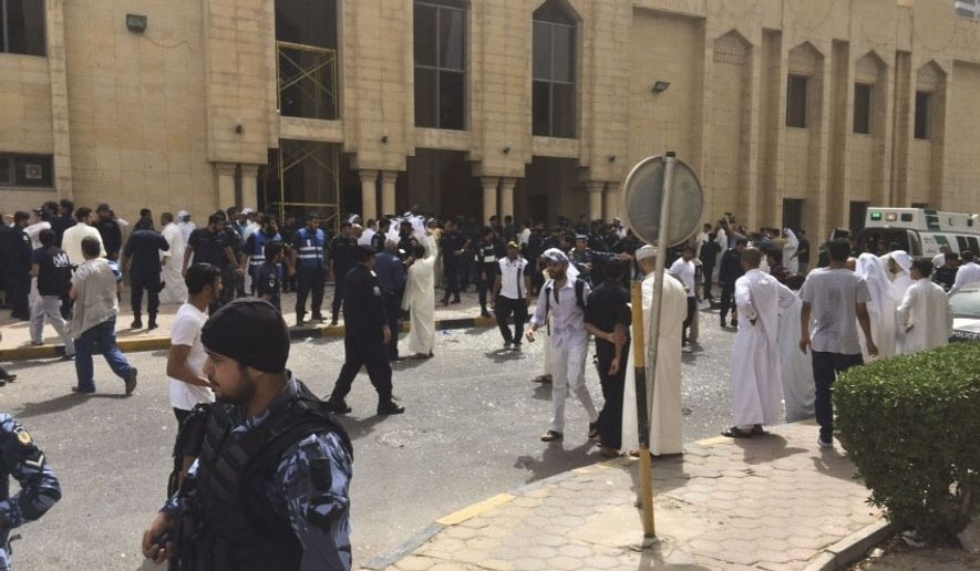 Security forces, officials and civilians gather outside of the Imam Sadiq Mosque after a deadly blast struck after Friday prayers in Kuwait City, Kuwait, Friday, June 26, 2015. There was no immediate claim of responsibility for what appears to be a bombing that targeted the Shiite mosque. (AP Photo)