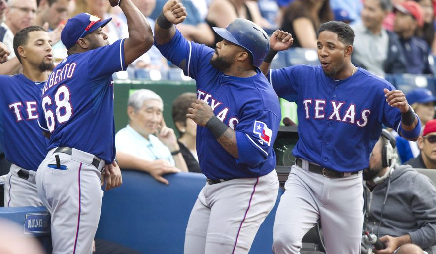Texas Rangers' Prince Fielder, center, is congratulated by teammates after he hit a home run against the Toronto Blue Jays in the first inning of a baseball game in Toronto, Friday, June 26, 2015. (Fred Thornhill/The Canadian Press via AP) MANDATORY CREDIT