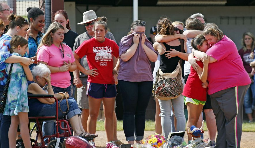 FILE - In this Sept. 27, 2014, file photo, family and friends mourn at a vigil held for former Wylie High School softball player Meagan Richardson, 19, at the Wylie High School softball field in Wylie, Texas. Russell Wayne Staley, the truck driver whose semitrailer crashed into a bus in Oklahoma and killed four members of the North Central Texas College softball team has been charged with four counts of first-degree manslaughter Thursday, June 25, 2015. (AP Photo/The Dallas Morning News, Louis DeLuca, File)