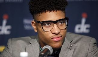 Washington Wizards' Kelly Oubre Jr. listens during an NBA basketball news conference, Friday, June 26, 2015, in Washington. Washington moved up four spots in the first round to get the Kansas freshman in a trade with the Atlanta Hawks, who selected Oubre with the 15th overall pick in the NBA draft the night before.. (AP Photo/Alex Brandon)