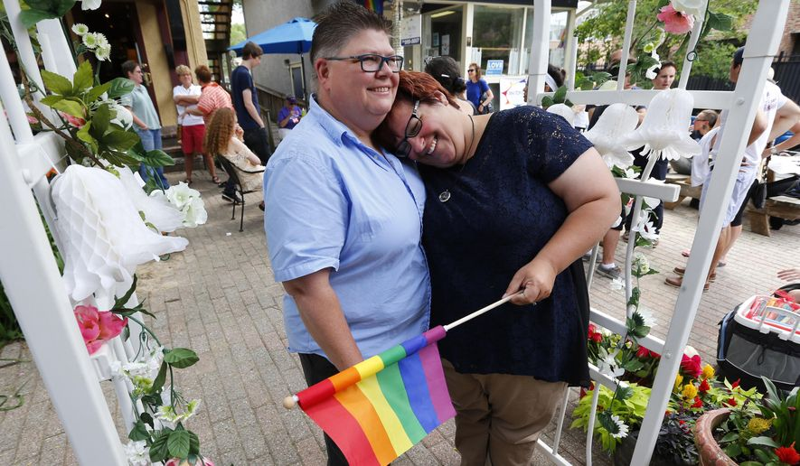 Jayne Rowse, left, and her partner April DeBoer celebrate in Ann Arbor, Mich., following a ruling by the U.S. Supreme Court that struck down bans on same sex marriage nationwide Friday, June 26, 2015. A judge who overturned Michigan's ban on gay marriage says he's willing to officiate at the marriage of the two Detroit-area nurses at the center of the groundbreaking case. (AP Photo/Paul Sancya)
