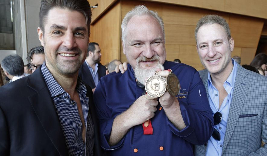 FILE - In this May 20, 2015 file photo, Celebrity chef Art Smith, shows off his James Beard Foundation awards with friends before a news conference, in Chicago. Smith of Chicago was planning to throw a massive wedding ceremony Sunday in Atlanta. He says it will become a celebration of the Supreme Court's historic same-sex marriage ruling Friday June 26, 2015.  (AP Photo/M. Spencer Green, File)