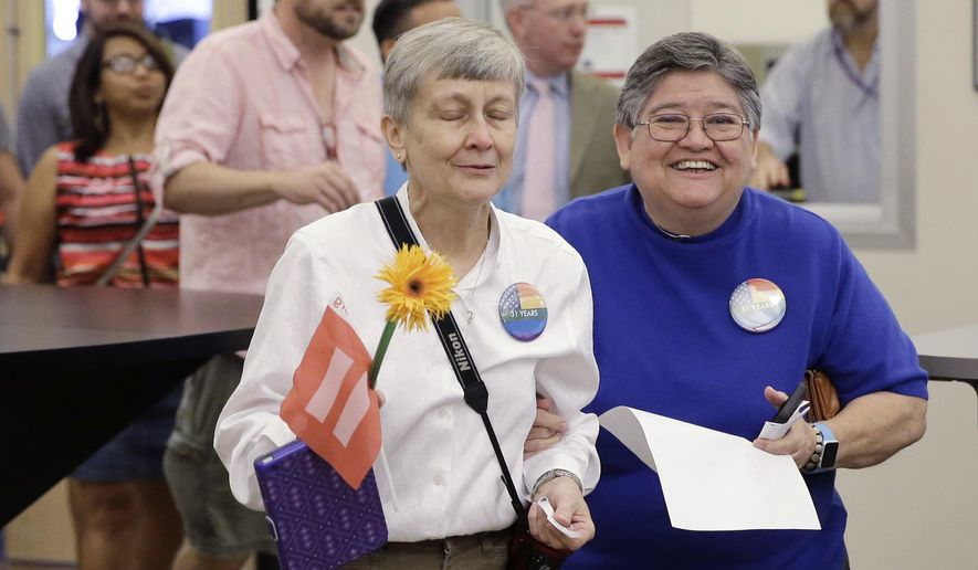 Jaque Roberts,  left, and her partner of 31 years, Carmelita Cabello, right, arrive to apply for  marriage license at the Travis County building after the U.S. Supreme Court ruled that  same-sex couples have the right to marry nationwide, Friday, June 26, 2015, in Austin, Texas. The court's 5-4 ruling means the remaining 14 states, in the South and Midwest, will have to stop enforcing their bans on same-sex marriage.(AP Photo/Eric Gay)