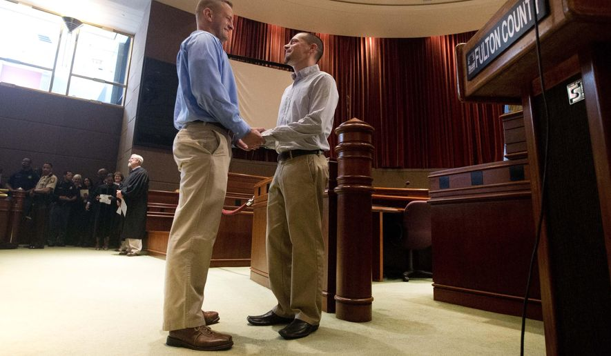 Shawn Brown, left, and Christian Marasko hold hands as they are married during a mass wedding at the Fulton County Government Center Friday, June 26, 2015, in Atlanta.  The U.S. Supreme Court on Friday ruled that there is a right to same-sex marriage in all 50 states across the country.  (AP Photo/John Bazemore)