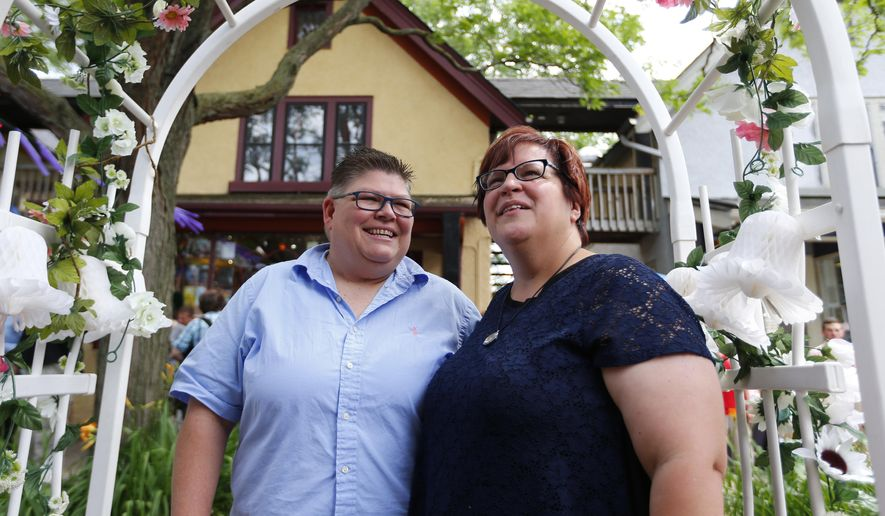 Jayne Rowse, left, and her partner April DeBoer celebrate in Ann Arbor, Mich., following a ruling by the US Supreme Court that struck down bans on same sex marriage nation wide Friday, June 26, 2015. A judge who overturned Michigan's ban on gay marriage says he's willing to officiate at the marriage of two Detroit-area nurses at the center of the groundbreaking case. (AP Photo/Paul Sancya)