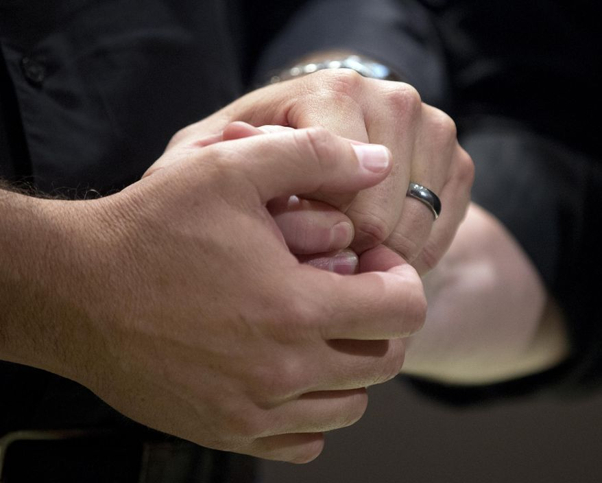Ed Cieslak and Richard Moye hold hands as they are married in a mass wedding at the Fulton County Government Center Friday, June 26, 2015, in Atlanta. A court in Atlanta started marrying gay couples Friday after the U.S. Supreme Court struck down Georgia's ban on same-sex marriage. (AP Photo/John Bazemore) **FILE**