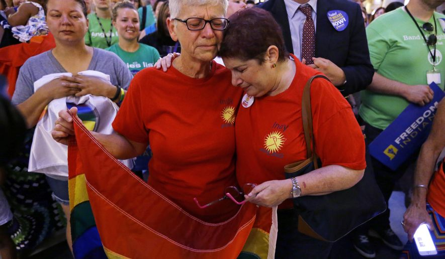 PFLAG members Betty Lynch, left, Carmel, Ind., and Annette Gross of Indianapolis, hug during a press conference in the Indiana Statehouse Rotunda in Indianapolis, Friday, June 26, 2015, after the Supreme Court declared that same-sex couples have a right to marry anywhere in the US.   (AP Photo/Michael Conroy)