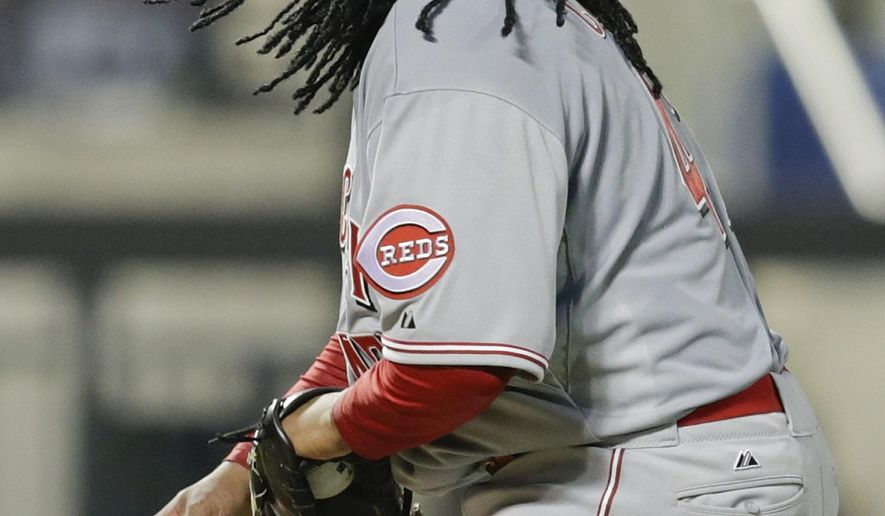 Cincinnati Reds starting pitcher Johnny Cueto picks up a rosin bag as he watches New York Mets' Dilson Herrera score on a bases-loaded walk during the fifth inning of a baseball game Friday, June 26, 2015, in New York. (AP Photo/Frank Franklin II)