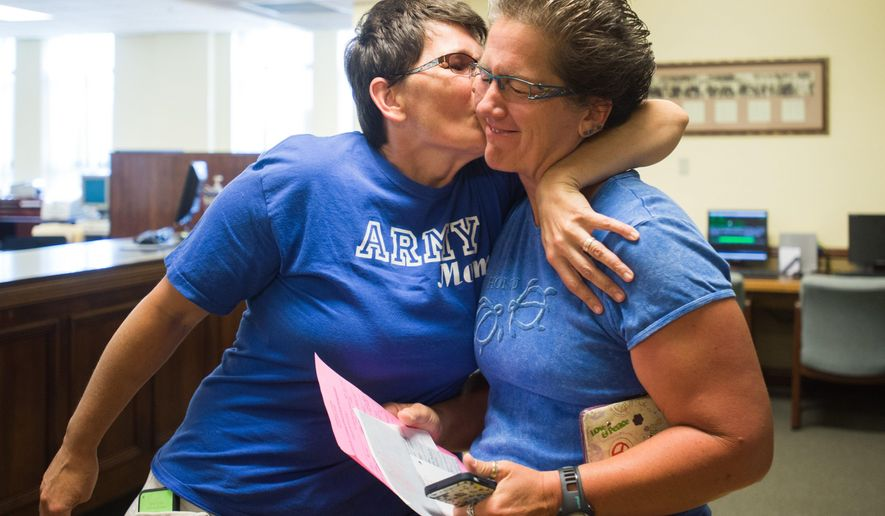 "Traci Bliss Panzner kisses Julie Ann Lake as they wait to receive their marriage license after the U.S. Supreme Court ruling in favor of same sex marriage at the Bay County Building on Friday June 26, 2015 in May City, Mich. Michigan Attorney General Bill Schuette says he will ""honor, respect and uphold"" the decision by the U.S. Supreme Court that overturned the state's ban on same-sex marriage. (Yfat Yossifor/The Bay City Times via AP) LOCAL TELEVISION OUT; LOCAL INTERNET OUT"
