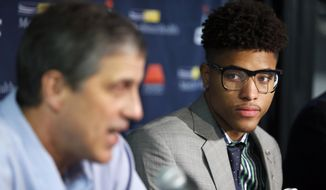 Washington Wizards' Kelly Oubre Jr., right listens to coach Randy Wittman speak during an NBA basketball news conference, Friday, June 26, 2015, in Washington. Washington moved up four spots in the first round to get the Kansas freshman in a trade with the Atlanta Hawks, who selected Oubre with the 15th overall pick in the NBA draft the night before. (AP Photo/Alex Brandon)