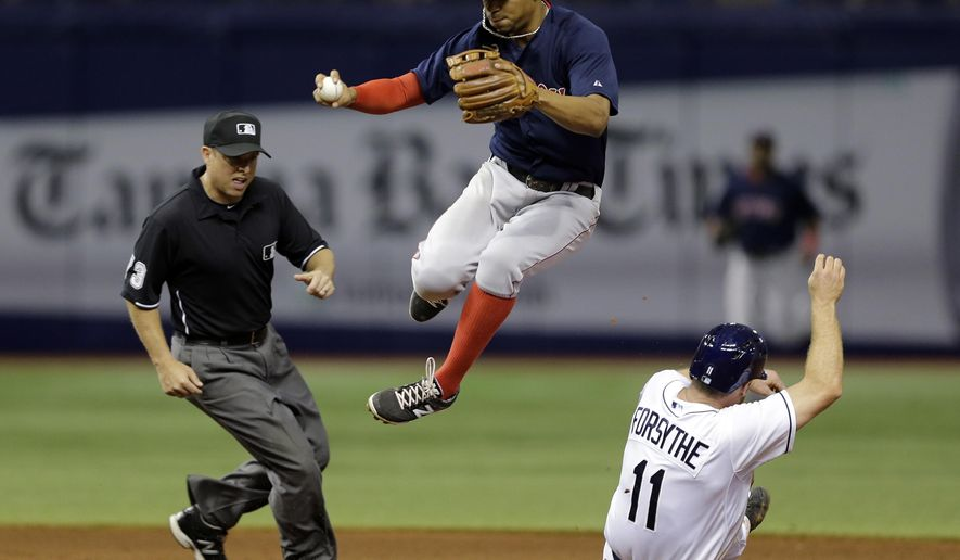 Boston Red Sox shortstop Xander Bogaerts, center, leaps over Tampa Bay Rays' Logan Forsythe (11) after forcing him at second base on a fielder's choice by Rays' Steven Souza Jr. during the sixth inning of a baseball game Friday, June 26, 2015, in St. Petersburg, Fla. Umpire Tripp Gibson, left, looks on. (AP Photo/Chris O'Meara)