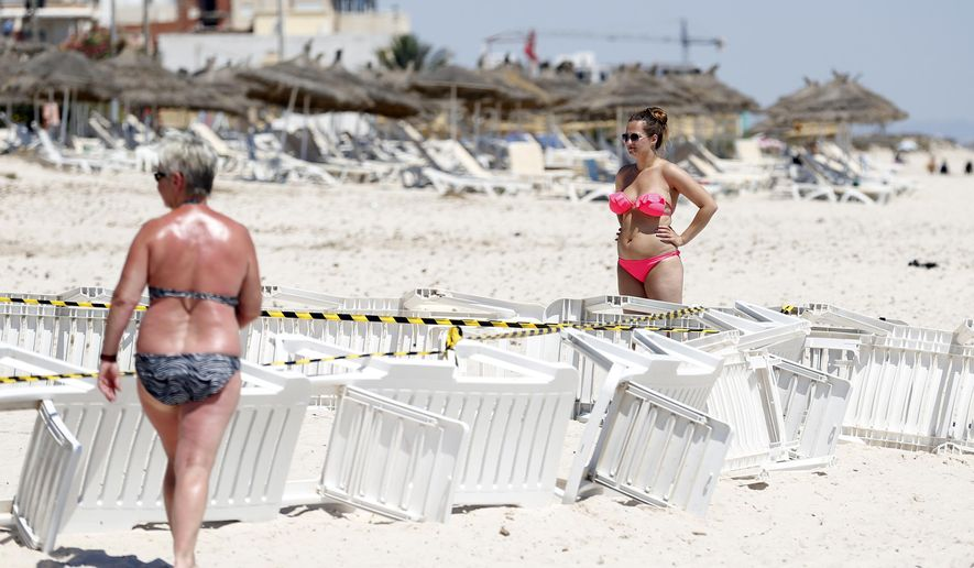 Tourists stand near the scene of a shooting attack on Friday in Sousse, Tunisia, Saturday, June 27, 2015. The morning after a lone gunman killed dozens of people at a beach resort in Tunisia, busloads of tourists are heading to the nearby Enfidha-Hammamet airport hoping to return to their home countries. (AP Photo/Darko Vojinovic)