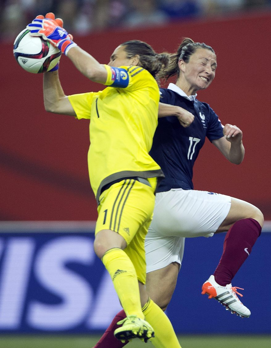 Germany goalkeeper Nadine Angerer, left, catches a shot as France's Gaetane Thiney moves in during the second-half of a quarterfinal match in the FIFA Women's World Cup soccer tournament, Friday, June 26, 2015, in Montreal, Canada. (Ryan Remiorz/The Canadian Press via AP) MANDATORY CREDIT