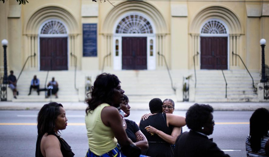 Lauretta Geddis, of Charelston, S.C., rear right, embraces Brenda T. Williams, of North Charelston, while waiting on line to enter Sen. Clementa Pinckney's funeral service, Friday, June 26, 2015, in Charleston. President Barack Obama delivered the eulogy at Pinckney's funeral Friday. (AP Photo/David Goldman)