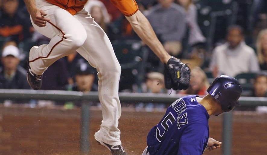 Colorado Rockies' Carlos Gonzalez (5) slides safely under the tag by San Francisco Giants pitcher Mike Broadway during the ninth inning of a baseball game, Friday, June 26, 2015, in San Francisco. Gonzalez scored on a wild pitch. (AP Photo/George Nikitin)