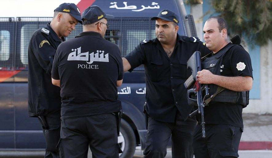 Tunisian police officers guard the street near the attacked Imperial Marhaba hotel in Sousse, Tunisia, Saturday, June 27, 2015. The morning after a lone gunman killed dozens of people at a beach resort in Tunisia, busloads of tourists are heading to the nearby Enfidha-Hammamet airport hoping to return to their home countries. (AP Photo/Darko Vojinovic)