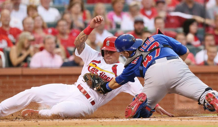 St. Louis Cardinals' Kolten Wong, left, is tagged out by Chicago Cubs catcher Miguel Montero during the first inning of a baseball game Friday, June 26, 2015, in St. Louis. (Chris Lee/St. Louis Post-Dispatch via AP)