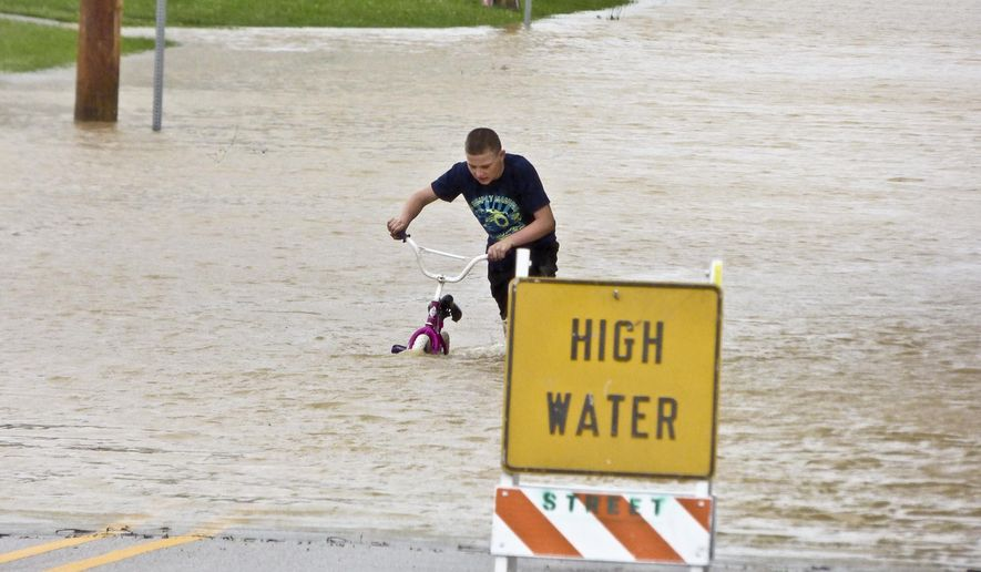 Cameron Miller, 12, pushes a bicycle through high water Saturday, June 27, 2015, on Wayne Street near East Jay Middle School in Portland, Ind. The city's downtown area was underwater for the second time in 10 days after several inches of rain fell Friday and Saturday. (Ray Cooney/The Commercial Review via AP) MUNCIE STAR PRESS OUT FORT WAYNE JOURNAL GAZETTE OUT