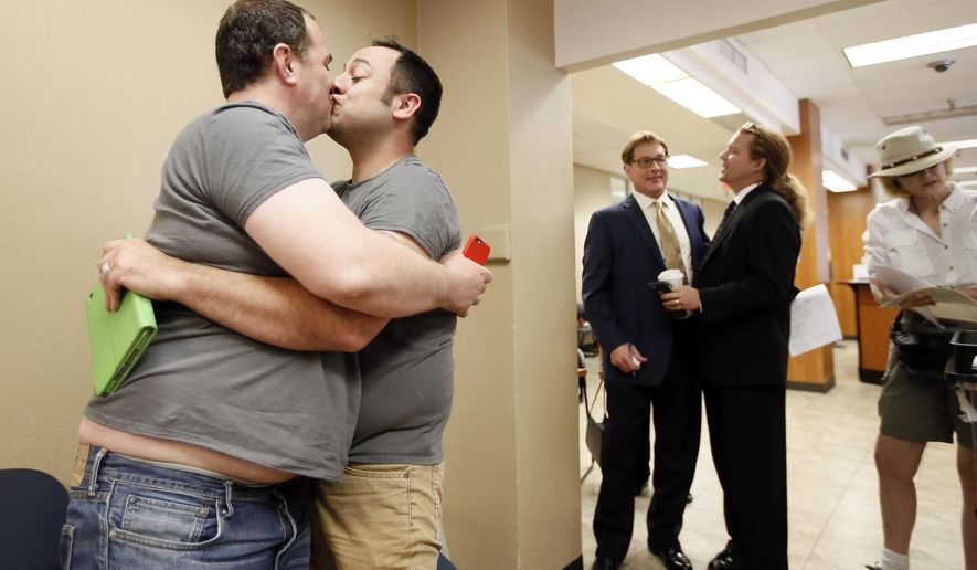 Kenneth Denson, left, and Gabriel Mendez kiss after hearing the U.S. Supreme Court news allowing same sex marriage Friday, June 26, 2015, in Dallas, at the county clerks office. (AP Photo/Tony Gutierrez)