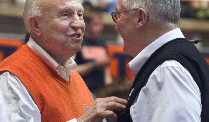 FILE - In this Jan. 18, 2014, file photo, former Illinois coach Lou Henson, left, chats with Rod Cardinal during Illinois' NCAA college basketball game in Champaign, Ill. Henson has been released from a Texas hospital and is scheduled to soon begin chemotherapy treatments. Henson's wife, Mary said that the 83-year-old retired coach is staying with family in Houston. He'll begin regular chemotherapy treatments before a planned return to his home in Champaign, Illinois, on July 12. The treatments will continue from there. (AP Photo/Robin Scholz, File)
