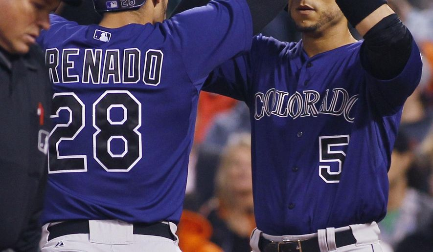 Colorado Rockies' Nolan Arenado (28) is greeted at the plate by Carlos Gonzalez after hitting a three-run home run against the San Francisco Giants during the sixth inning of a baseball game, Friday, June 26, 2015, in San Francisco. (AP Photo/George Nikitin)