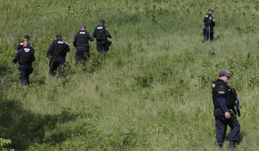 New York State officers search for convicted murderers Richard Matt and David Sweat, Friday, June 26, 2015, in Malone, N.Y. Matt was shot and killed by a Border Patrol agent in a wooded area about 30 miles from the prison on Friday, and Sweat is on the run, authorities said. (AP Photo/Mary Altaffer)