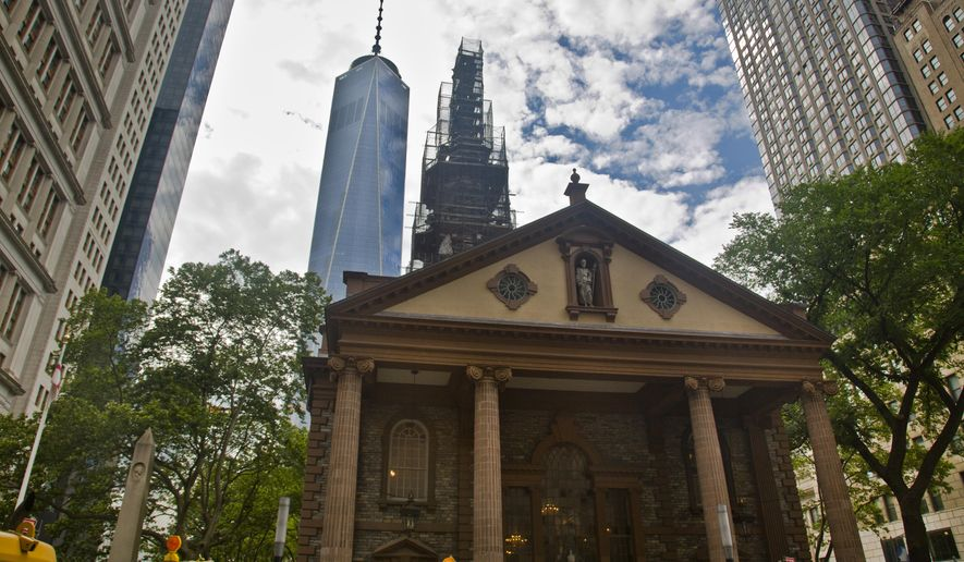 """The  World Trade Center looms behind St. Paul's Chapel with its steeple wrapped in scaffolding for repairs, Thursday, June 25, 2015, in New York.  The winner of a new competition open to people of all faiths called """"The Reconciliation Preaching Prize,"""" will have the privilege of delivering an original sermon on Sept. 11 at the chapel near ground zero.  It was turned into a makeshift memorial shrine and became a place of rest and renewal for volunteers and responders, following the terrorist attacks that brought down the twin towers. (AP Photo/Bebeto Matthews)"""