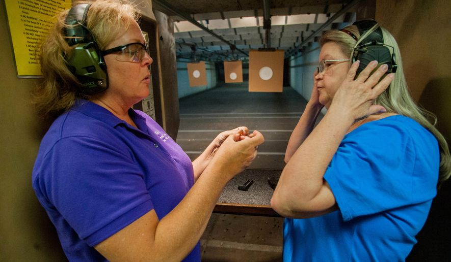 ADVANCE FOR SATURDAY, JUNE 27, 2015 AND THEREAFTER - In this June 18, 2015 photo, Julie Delp instructs Paula Martinez, right, during a meeting of The Well Armed Woman gun club at Thunder Alley indoor shooting range in Lincoln, Neb. The club meets twice monthly to work on their skills and grow as shooters. (Amber Baesler/The Journal-Star via AP)