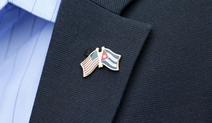 A member of the U.S. Senate delegation wears a crossed flag pin representing the US and Cuban national flags, at a press conference in Havana, Cuba, Saturday, June 27, 2015.  The U.S. Senate bipartisan delegation spoke to the media during their visit to Cuba as the two countries move toward reopening embassies and restoring long-strained diplomatic ties. (AP Photo/Desmond Boylan)