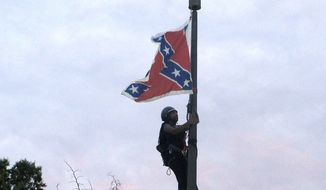 Bree Newsome of Charlotte, N.C., climbs a flagpole to remove the Confederate battle flag at a Confederate monument in front of the Statehouse in Columbia, S.C., on Saturday, June, 27, 2015. She was taken into custody when she came down. The flag was raised again by capitol workers about 45 minutes later. (AP Photo/Bruce Smith)